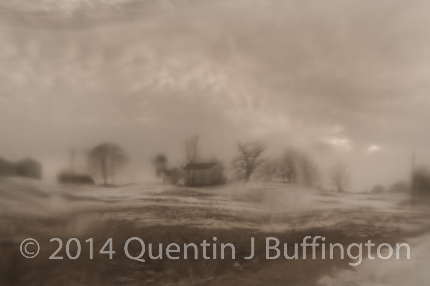 A sad burned out farmhouse as shot through a paper thin sheet of ice.