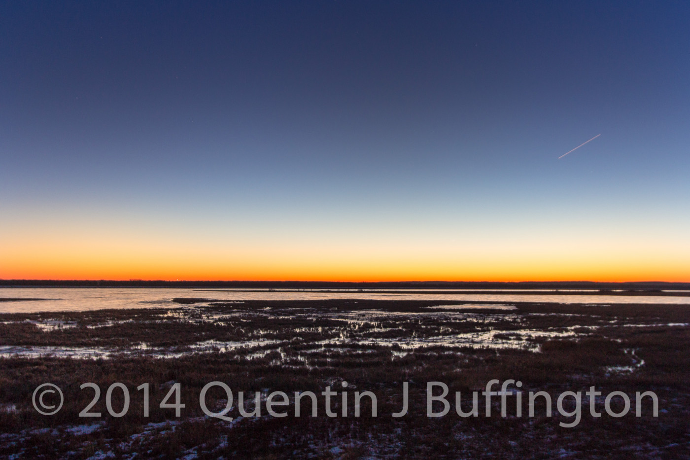 The thin line of color painted by the sun as it slips beneath the horizon on a cold wintery night.