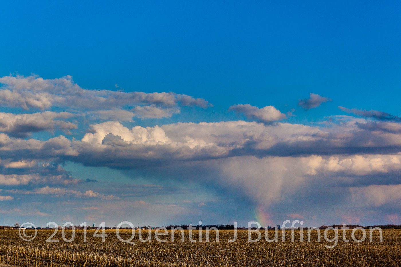 A distant spring cloudburst throwing a rainbow in the late afternoon sun.