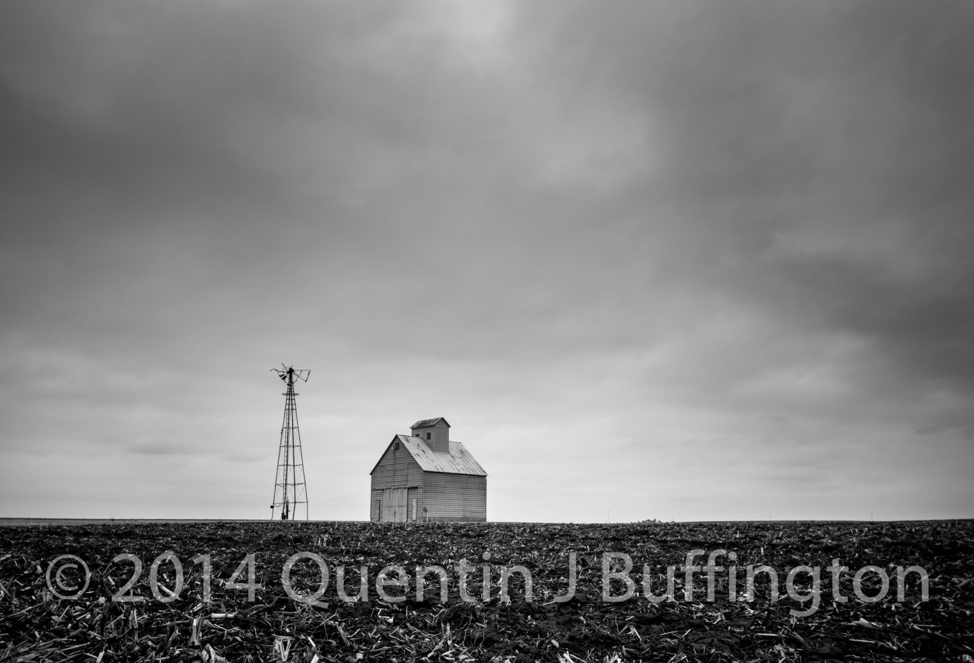 An old windmill and barn crib standing lonely and barren on the prairie.